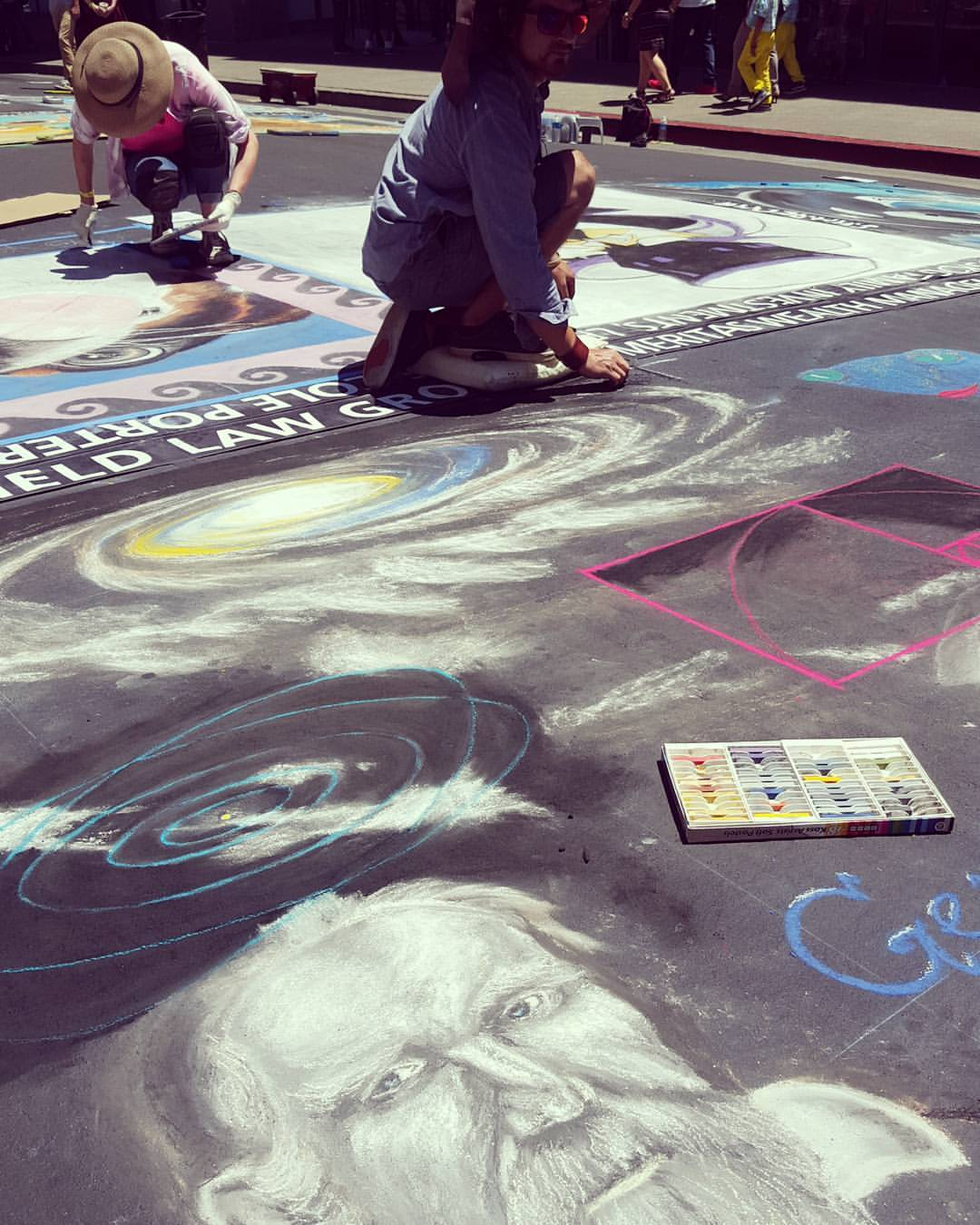 Artist in process of creating street painting